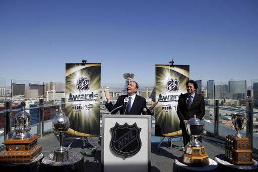 FILE - In this April 6, 2009, file photo, NHL commissioner Gary Bettman, center, gestures as he comments on the weather during a news conference  to promote the NHL Awards Show, in Las Vegas. Once perhaps an unlikely leader for the good ol' hockey game with its roots north of the border, the 65-year-old Jewish lawyer from New York has become one of the most powerful and long-lasting forces in professional sports.