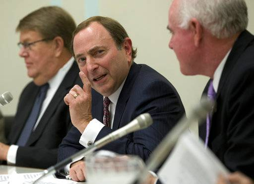 FILE - In this April 24, 2013, file photo, NHL Commissioner Gary Bettman, center, flanked by USA Hockey Executive Director Dave Ogrean, left, and Rep. Pat Meehan, R-Pa., gestures as he speaks during a congressional hockey caucus briefing on Capitol Hill in Washington. Bettman doesn't have boundaries. The NHL commissioner whose cross-border league is made up of 24 teams in the United States and seven from Canada doesn't put his work on hold for life or vice versa.