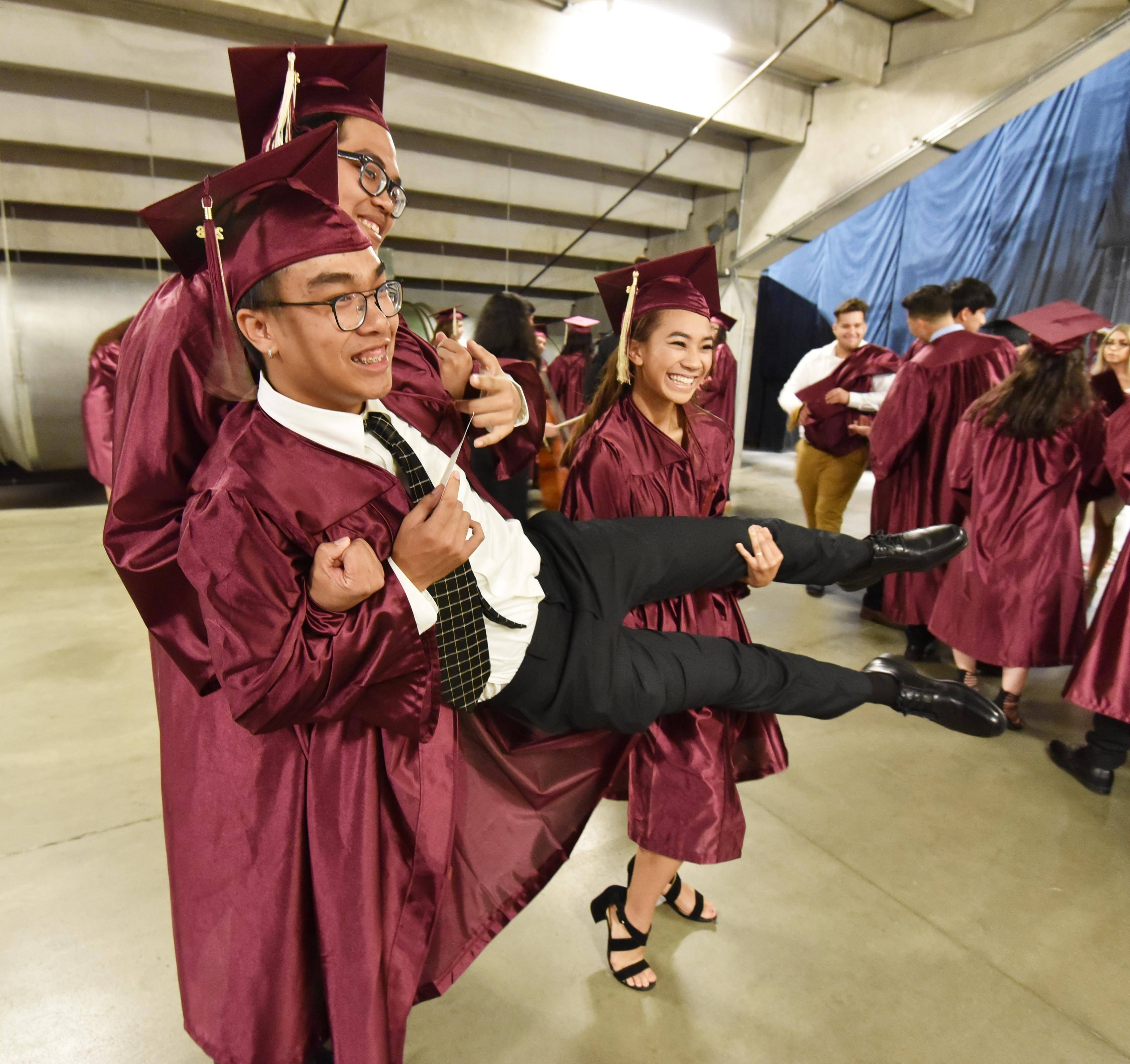 Drake Phamanivong is lifted by fellow graduates Matthew Pettineo and Rachel Phimmavong as Kacy Perfors takes their photo before the Elgin High School graduation ceremony Saturday at the Sears Centre in Hoffman Estates.