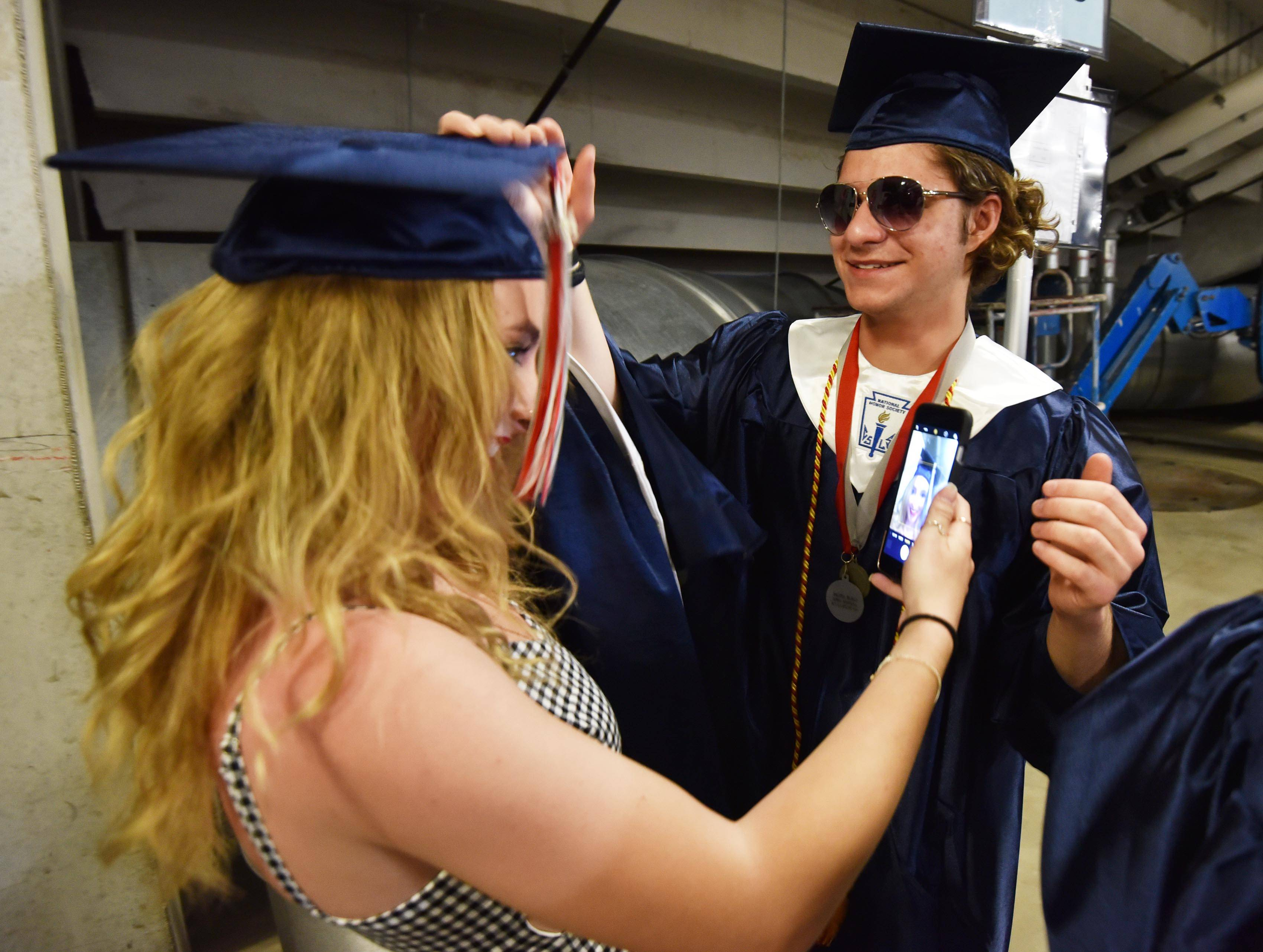 Ethan Schneider helps his sister Isabella with her cap before the South Elgin graduation ceremony at the Sears Centre in Hoffman Estates Saturday.