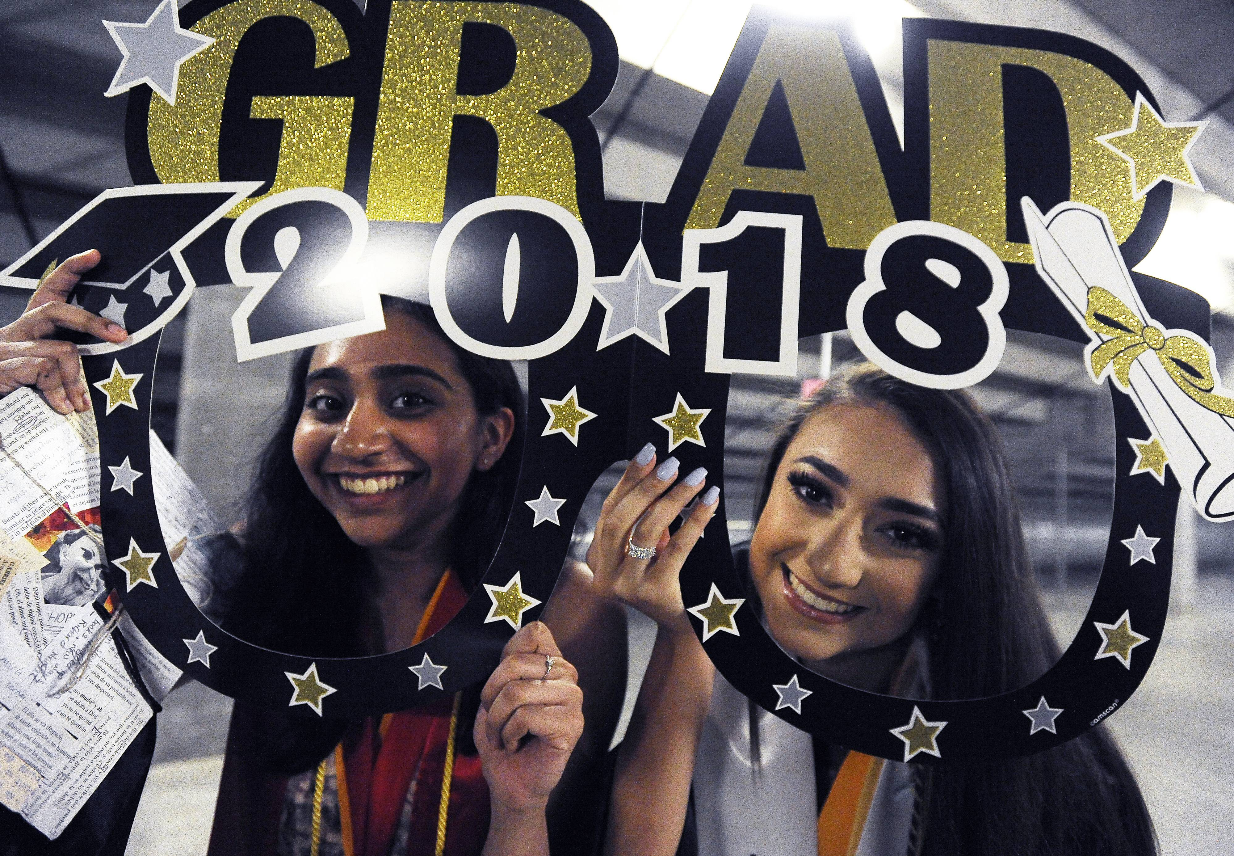 Wardah Mohamed, 18, and Alyssa Perez, 18, both of Streamwood hold up a sign of the times as they prepare to graduate at the 38th commencement ceremony of Streamwood High School at the Sears Centre in Hoffman Estates on Saturday.