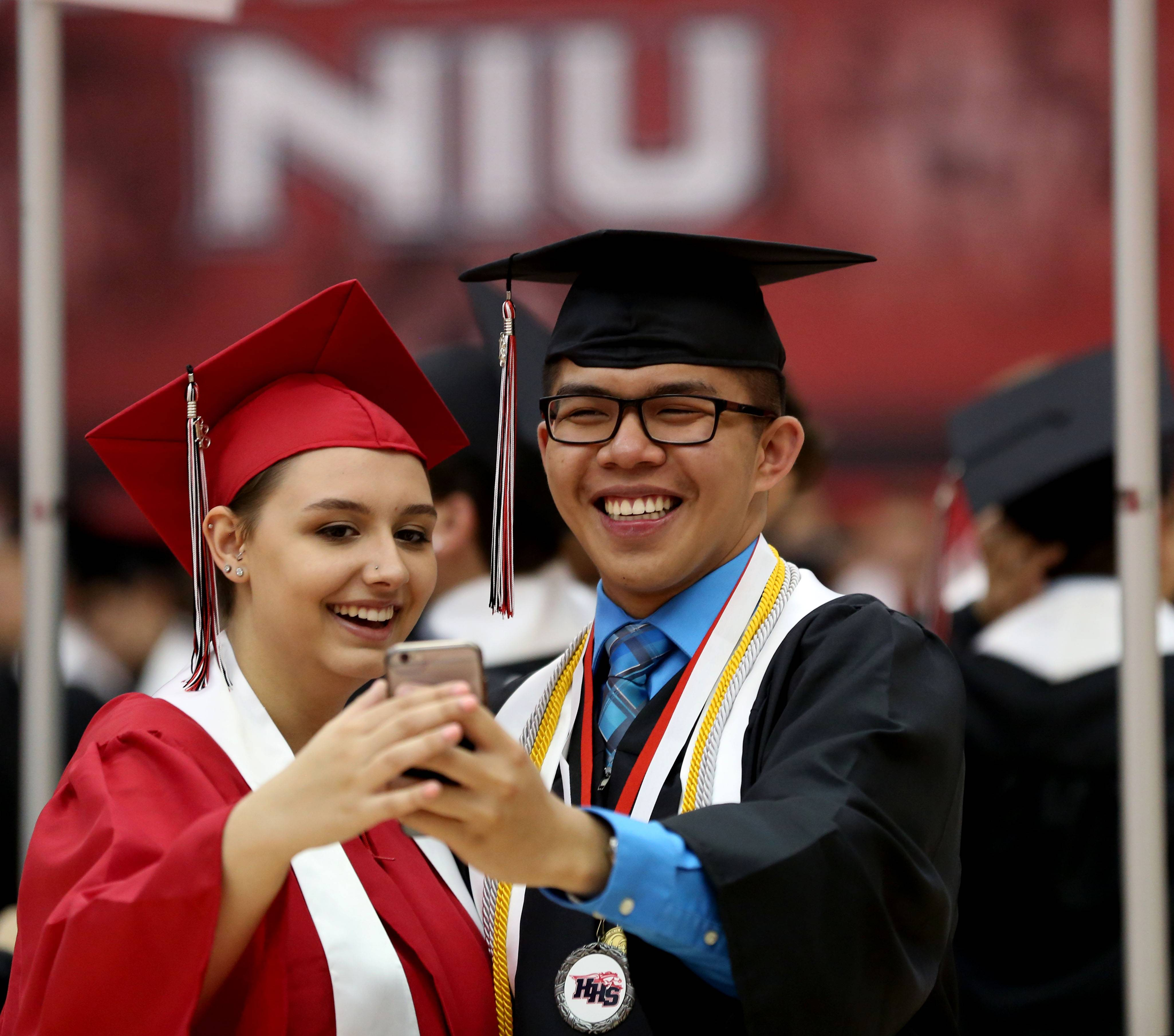 Claire Lenihan, left, of Huntley takes a selfie with classmate Xavier Lee of Lake in the Hills before they line up to march at the commencement program for Huntley High School at the Convocation Center on the campus off Northern Illinois University in DeKalb on Saturday, May 26.