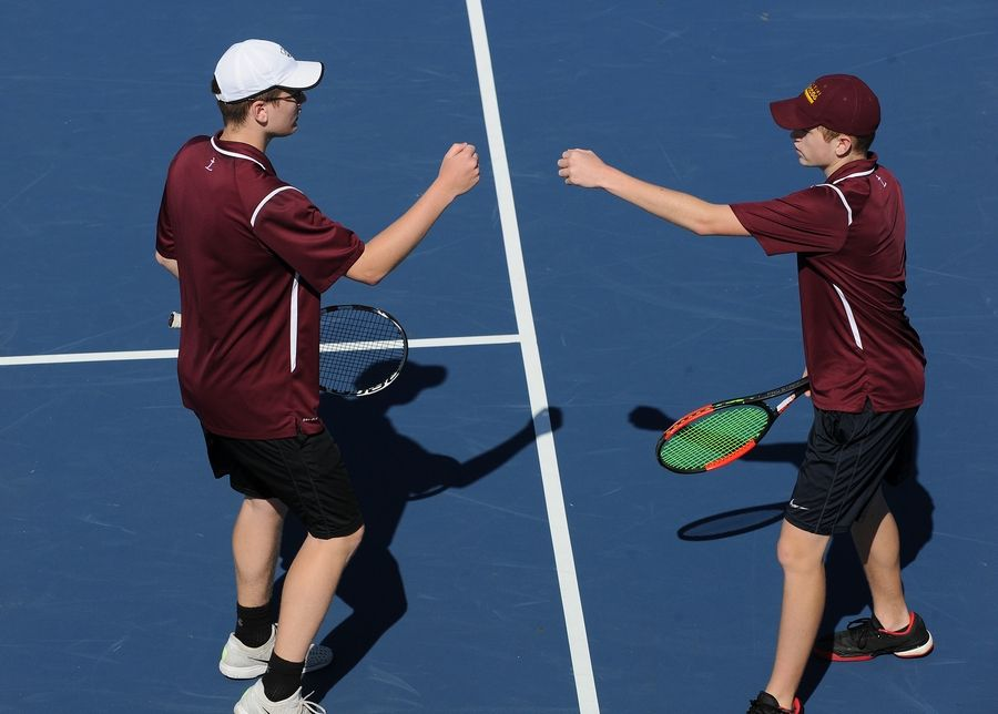 Montini's David Batka (right) and his brother Thomas come together after a shot back to the competition in boys state tennis class 1A doubles division at Hersey High School on Saturday.