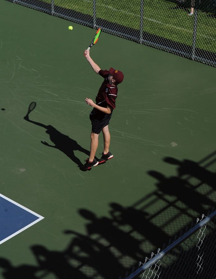 Montini's David Batka hits a shot back to the competition in boys state tennis class 1A doubles division at Hersey High School on Saturday.