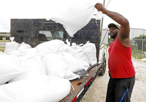 Travis Lee loads filled sand bags onto a truck bed as he and a co-worker prepare to protect the storage company they work at, Saturday, May 26, 2018 in Gulfport, Miss. They and many other Gulf Coast residents are preparing for Subtropical Storm Alberto to make its way through the Gulf of Mexico to land. The slow moving storm is threatening to bring heavy rainfall, storm surges, high wind and flash flooding this holiday weekend.