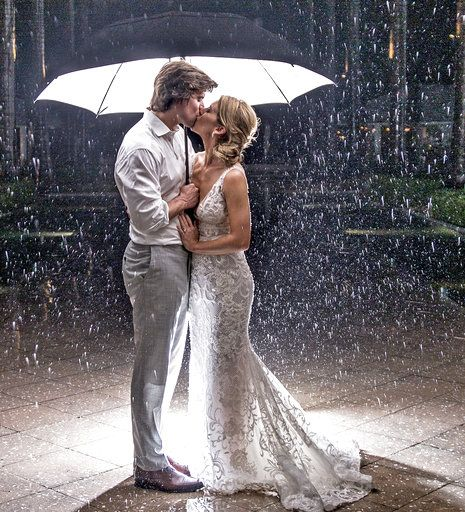 In this Saturday, May 26, 2018, photo provided by the Florida Keys News Bureau, Hannibal and Emily Baldwin pose for a wedding photo under an umbrella outside the Casa Marina Resort in Key West, Fla. The Tampa, Fla., couple had planned an outdoor wedding, but the evening ceremony and reception were moved inside due to rain bands emanating from Subtropical Storm Alberto. The center of the storm passed far enough west of the contiguous Florida Keys to avoid placing the region under a tropical storm warning. (Bob Care/Florida Keys News Bureau via AP)