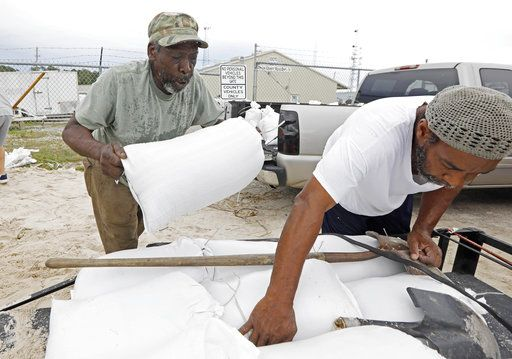 Tommy Whitlock, left, places a filled sand bag onto his trailer at a Harrison County Road Department sand bag location, as his friend Joseph Buckner adjusts the load while preparing for Subtropical Storm Alberto to make its way through the Gulf of Mexico in Gulfport, Miss., Saturday, May 26, 2018. Whitlock, who lives near a creek wants to keep the spill off water from entering his home. The slow moving storm is threatening to bring heavy rainfall, storm surges, high wind and flash flooding this holiday weekend. Several similar setups were placed throughout the Mississippi Gulf Coast to help residents protect their property. The sandbagging process was left to the residents.