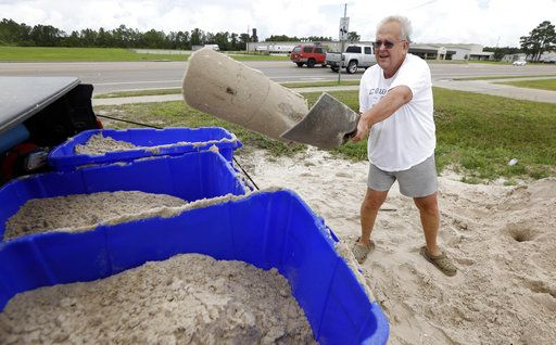 George Estes tosses sand into storage tubs at a Harrison County Road Department sand bagging location, that he will take back to his law office in downtown Gulfport, Miss., and will enlist help to fill bags that he will place by his office doors and plate glass window, while preparing for Subtropical Storm Alberto to make its way through the Gulf of Mexico in Gulfport, Miss., Saturday, May 26, 2018. The slow moving storm is threatening to bring heavy rainfall, storm surges, high wind and flash flooding this holiday weekend.