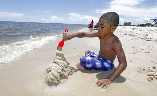 Tyler Ray Wells, 4, builds a sand castle by the water on Biloxi Beach in Biloxi, Miss., Saturday, May 26, 2018, as Subtropical Storm Alberto slowly makes its way through the Gulf of Mexico. The storm is threatening to bring heavy rainfall, storm surges, high wind and flash flooding this holiday weekend.