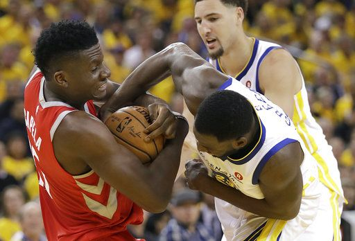 Houston Rockets center Clint Capela, left, tries to control the ball against Golden State Warriors forward Draymond Green, right, and guard Klay Thompson, rear, during the first half of Game 6 of the NBA basketball Western Conference Finals in Oakland, Calif., Saturday, May 26, 2018.