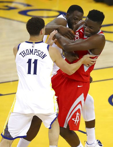 Houston Rockets center Clint Capela, right, tries to control the ball between Golden State Warriors guard Klay Thompson (11) and forward Draymond Green during the first half of Game 6 of the NBA basketball Western Conference Finals in Oakland, Calif., Saturday, May 26, 2018.