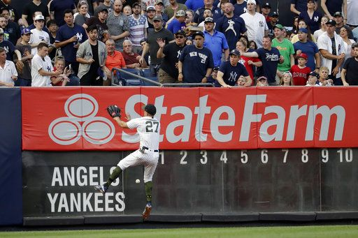 New York Yankees left fielder Giancarlo Stanton (27) prepares to hit the wall while fielding a double from Los Angeles Angels' Mike Trout during the first inning of a baseball game Saturday, May 26, 2018, in New York.