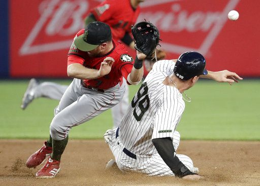 Los Angeles Angels second baseman Zack Cozart, left, is unable to catch a throw from catcher Jose Briceno on a stolen base by New York Yankees' Aaron Judge during the third inning of a baseball game Saturday, May 26, 2018, in New York. Judge moved to third on the play.