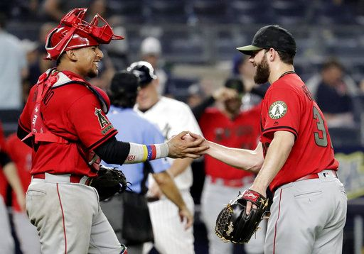 Los Angeles Angels catcher Jose Briceno, left, and relief pitcher Cam Bedrosian celebrate after the Angels defeated the New York Yankees 11-4 in a baseball game Saturday, May 26, 2018, in New York.