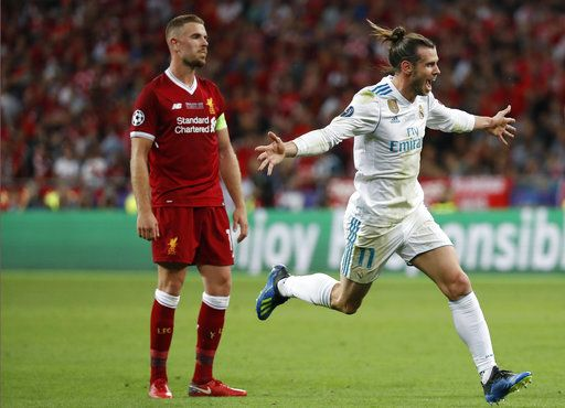 Real Madrid's Gareth Bale celebrates past Liverpool's Jordan Henderson, left, after scoring his side's third goal during the Champions League Final soccer match between Real Madrid and Liverpool at the Olimpiyskiy Stadium in Kiev, Ukraine, Saturday, May 26, 2018.