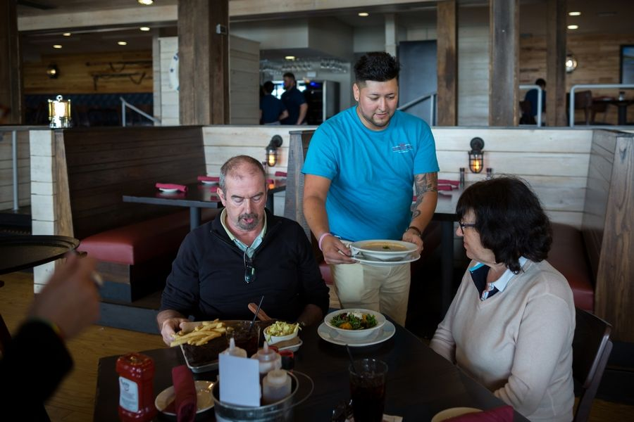 Server Gustavo Salines delivers meals to a couple visiting from Britain at Skull Creek Dockside Waterfront Restaurant on Hilton Head Island, S.C. Staffing at the restaurant is down 10 percent because of a labor shortage.
