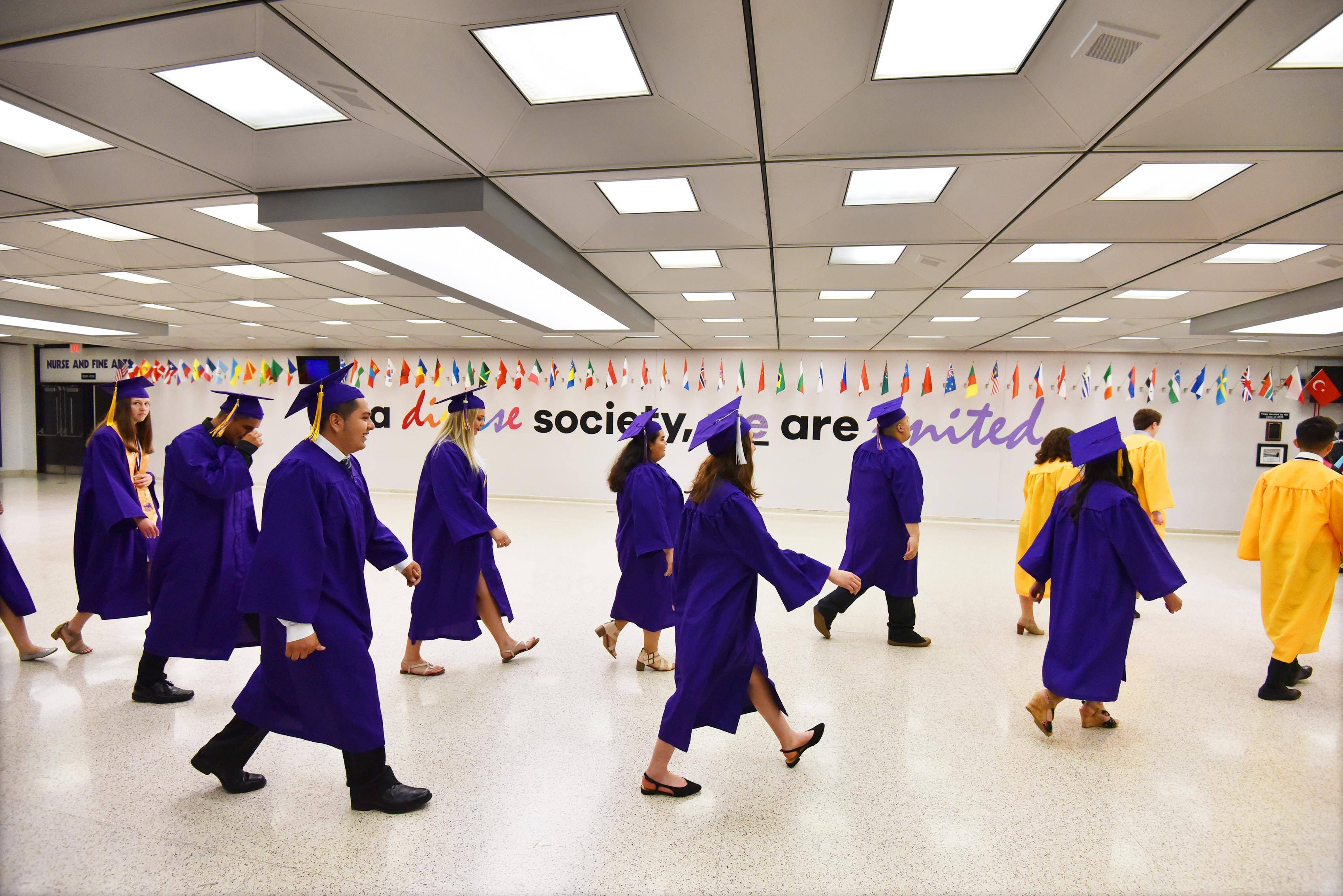 The Rolling Meadows High School graduating class walks to the ceremony Sunday at the school.