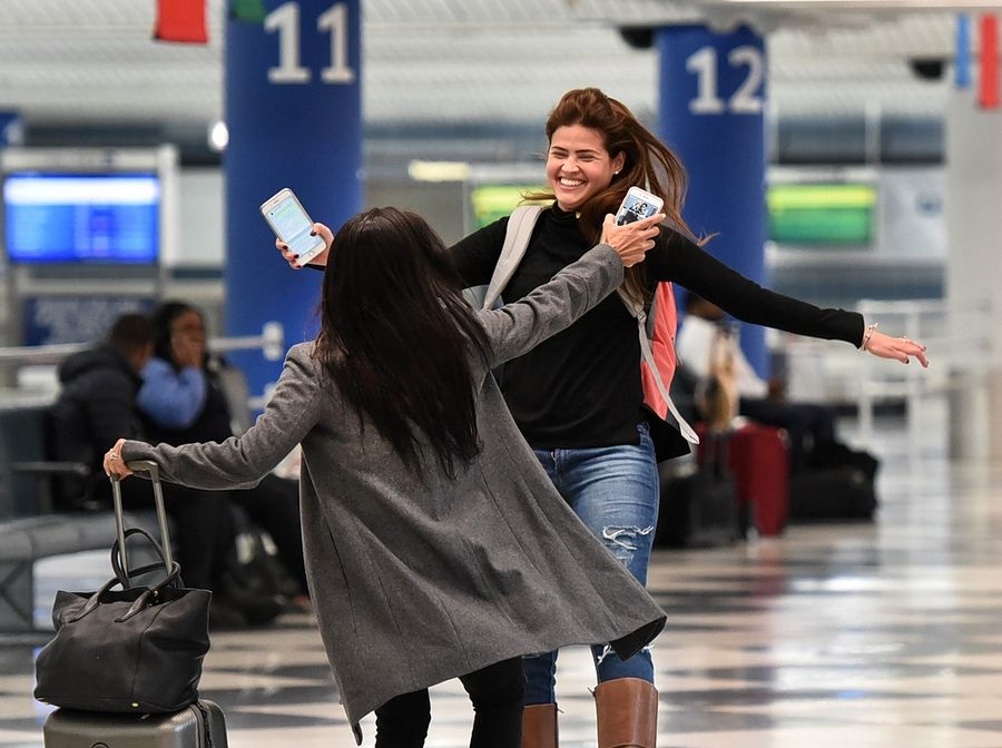 Catarina Pinto, right, and Geovanna Mofato, both of Rio de Janeiro, embrace on the lower level of O'Hare International Airport's Terminal 1.