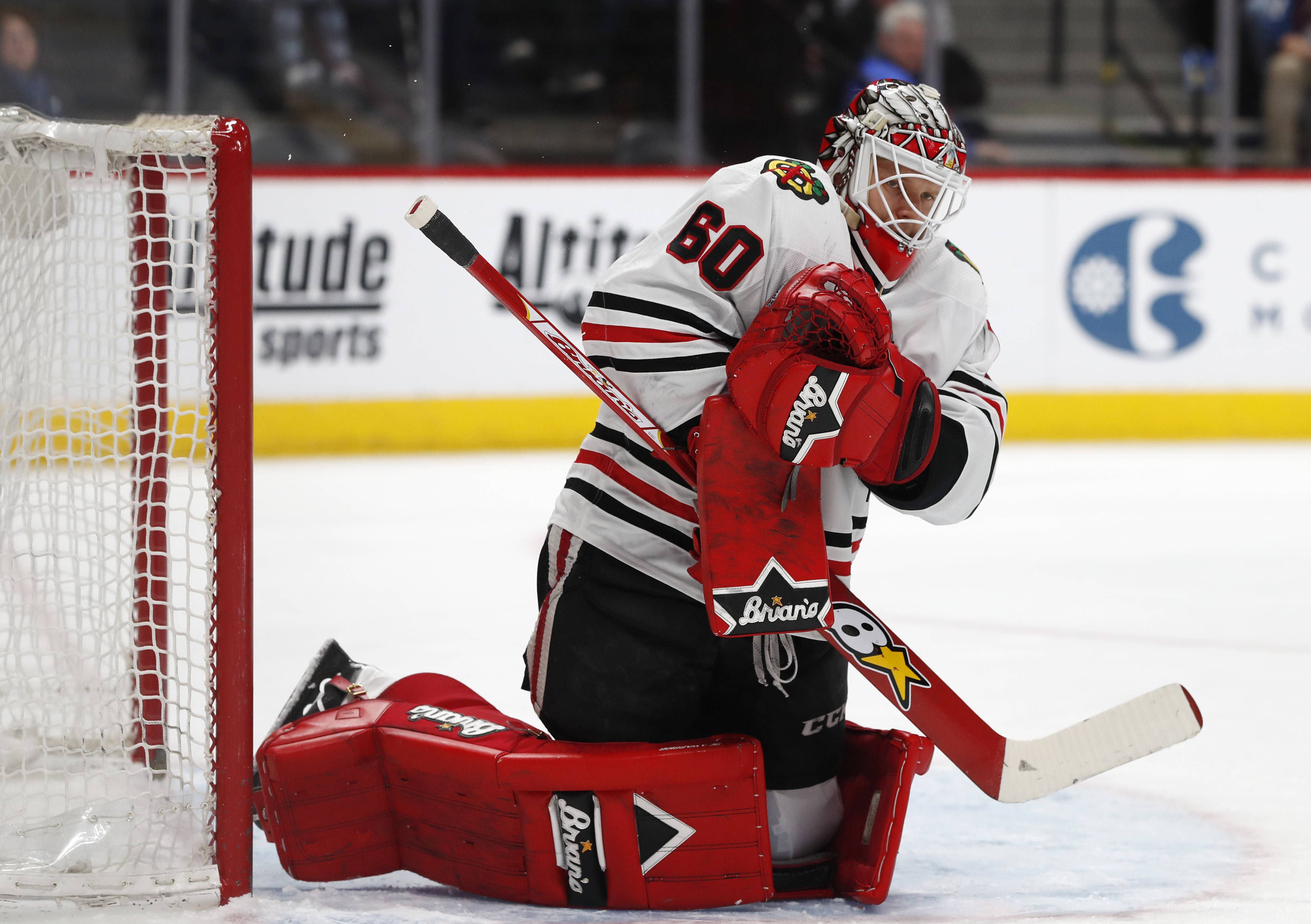 Chicago Blackhawks goaltender Collin Delia makes a save of a shot off the stick of a Colorado Avalanche player in the first period of an NHL hockey game Friday, March 30, 2018, in Denver.