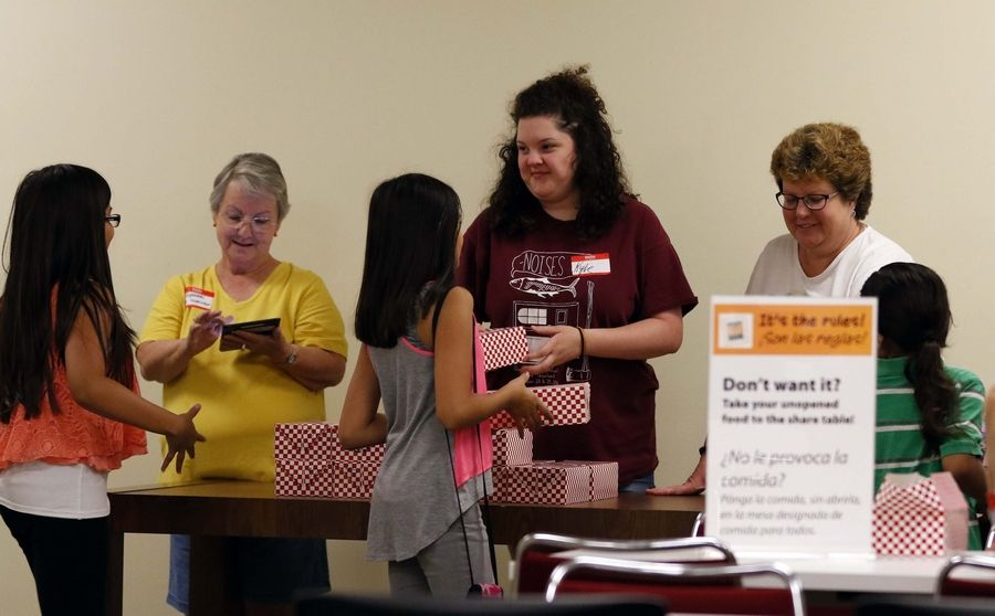 From left, Elizabeth Mike of Carpentersville and Kylie Saunders, 17, and her mom Lisa, both of Algonquin, help hand out lunches last summer at the Fox River Valley Library District in East Dundee.