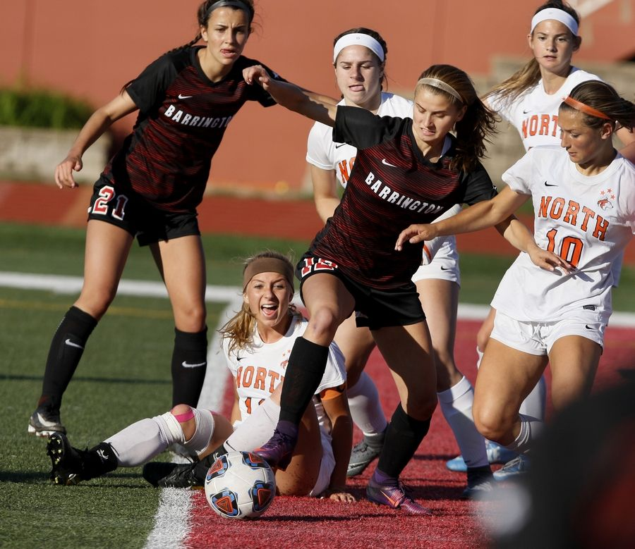 Naperville North's Alyssa Siebers yells from the ground while Barrington's Ashley Prell gains possession of the ball during the Class 3A girls state soccer semifinals at North Central College on Friday.
