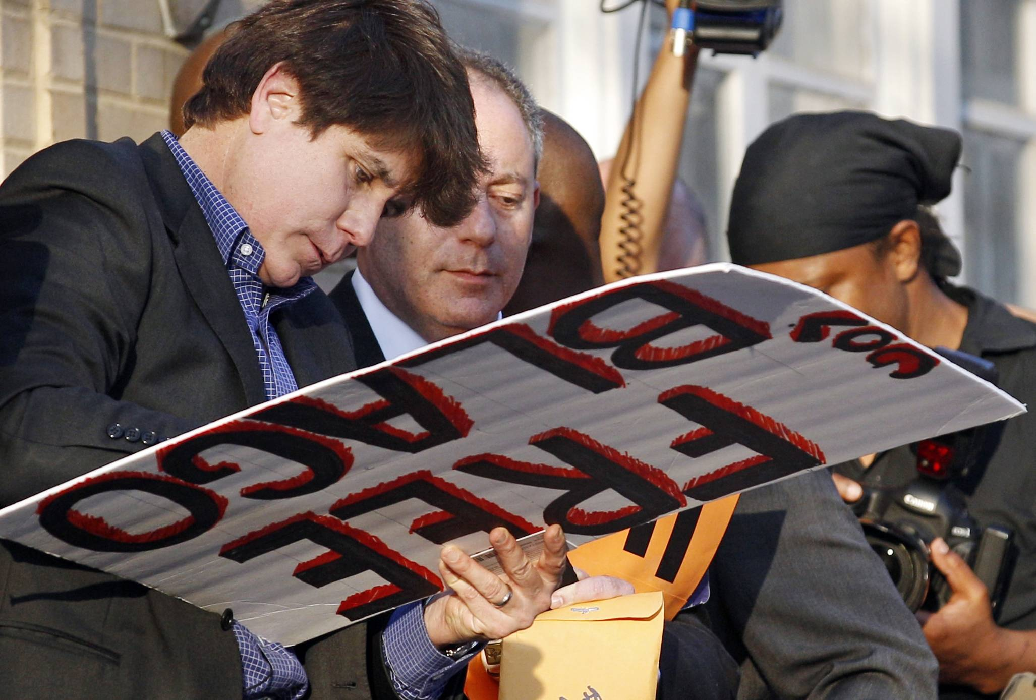 Former Illinois Gov. Rod Blagojevich autographs a 'Free Gov. Blago' sign at his home in Chicago the day before he would report to prison in 2012.