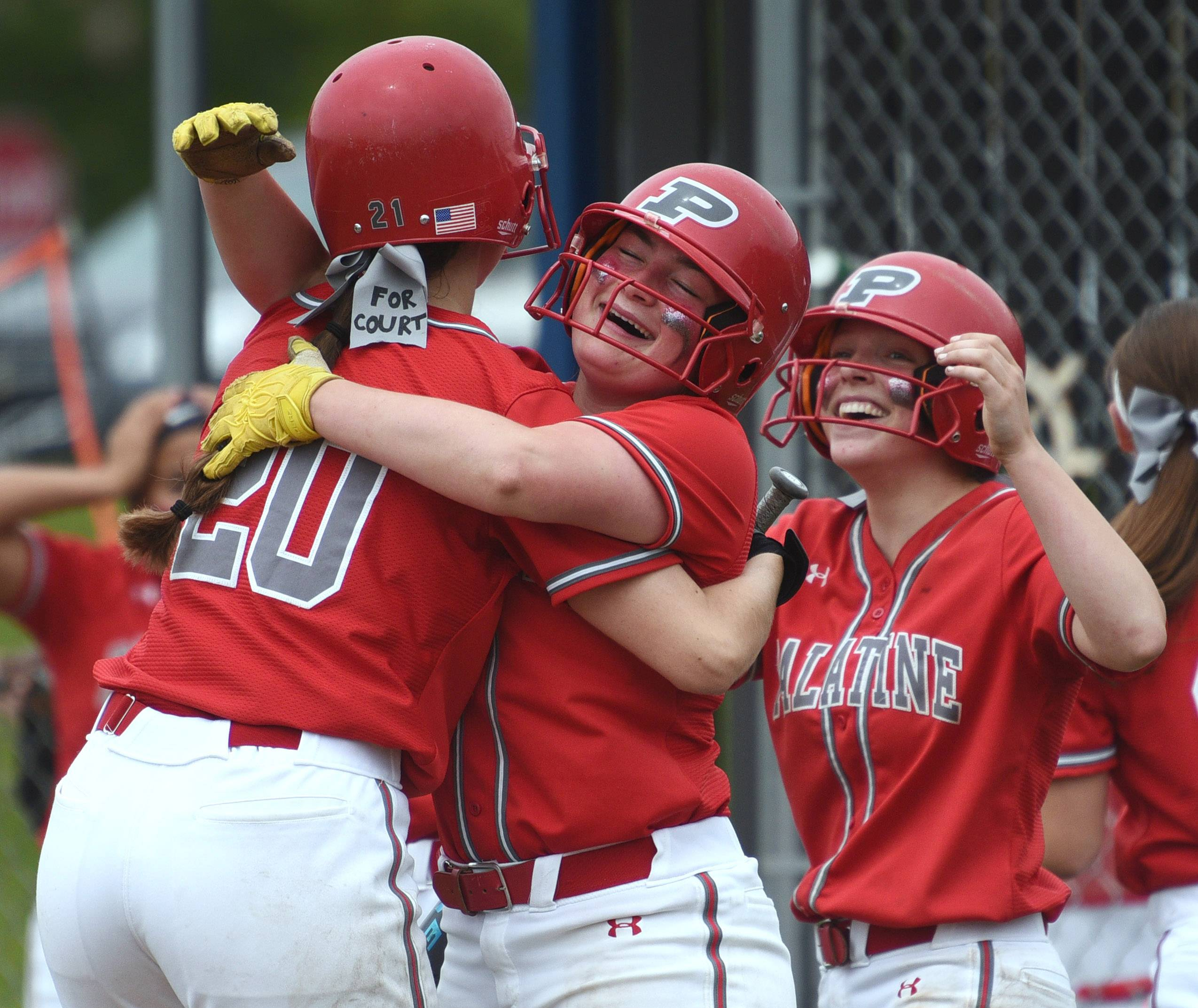 After hitting a grand slam in the seventh inning, Palatine's Amanda Stanczuk (20) is congratulated by teammates Grace Huff and Maddie Craver, right, during Saturday's Class 4A sectional championship game against host Warren.