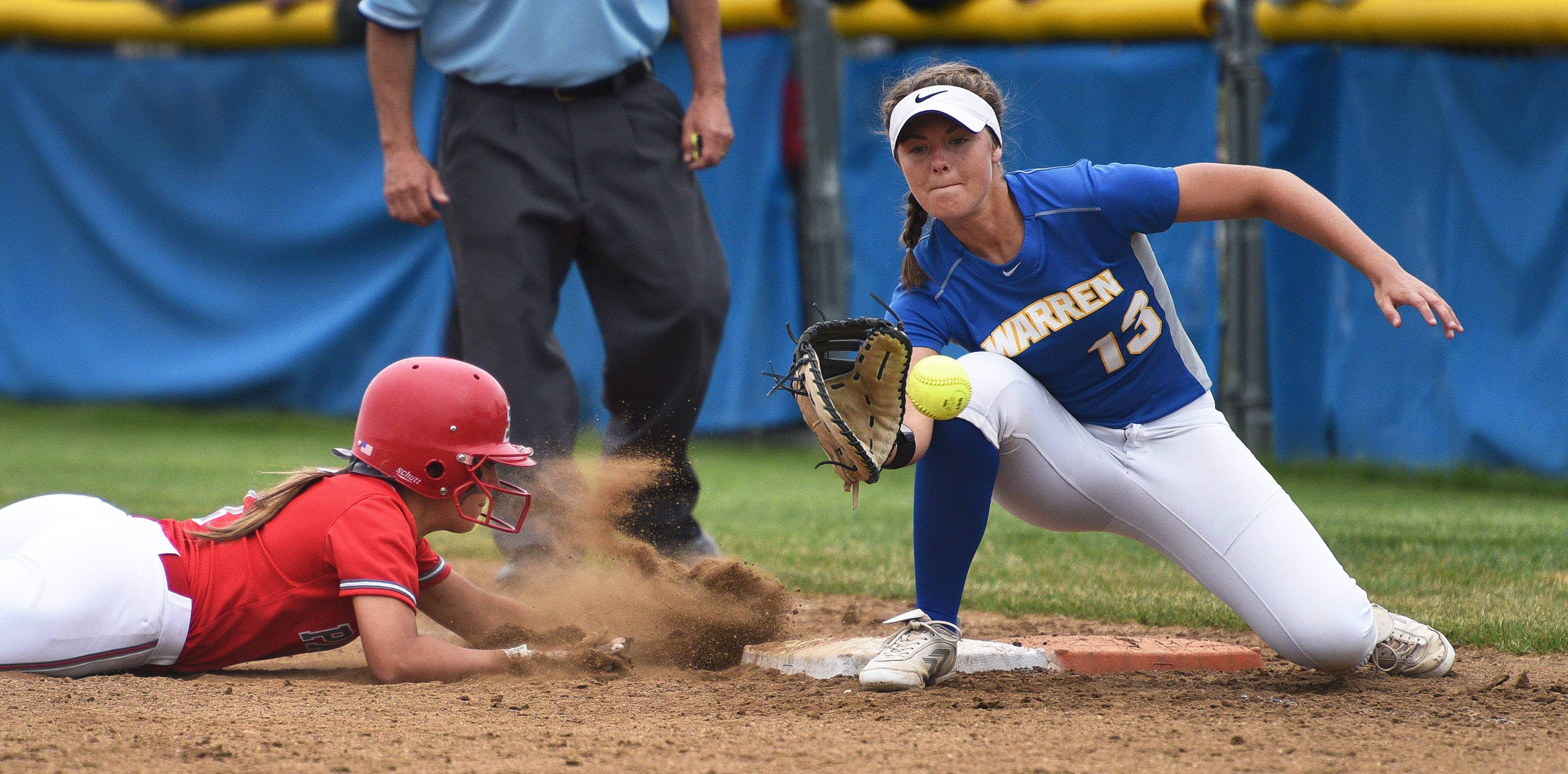 Palatine's Brittany Padden, left, slides safely back to first base as Warren's Kayla Nommensen waits for the pickoff throw during Saturday's Class 4A sectional championship softball game in Gurnee.