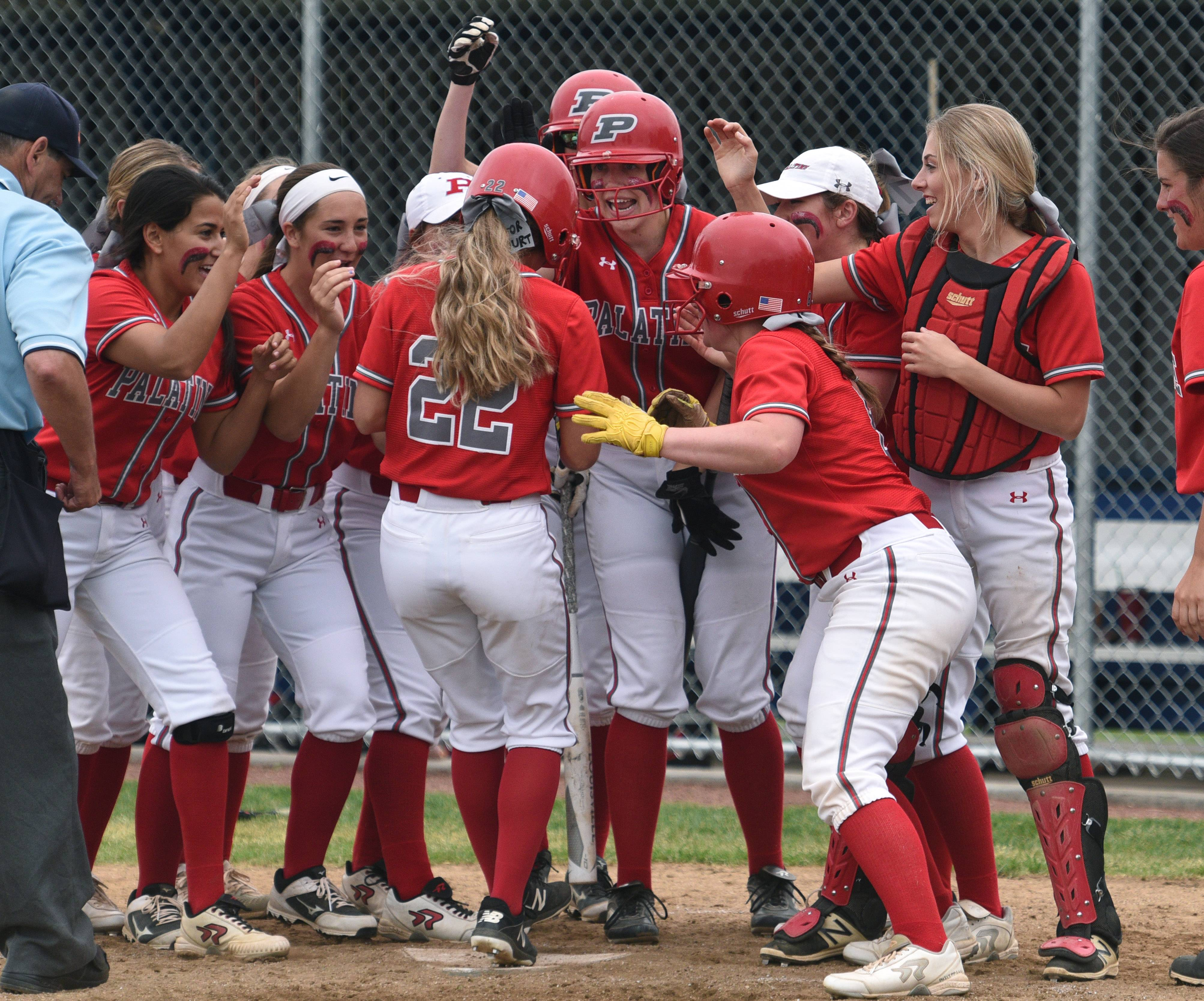 Palatine's Emily Parrott (22) is greeted at home following her third inning 2-run homer against Warren on Saturday in the Class 4A girls softball sectional championship game in Gurnee.