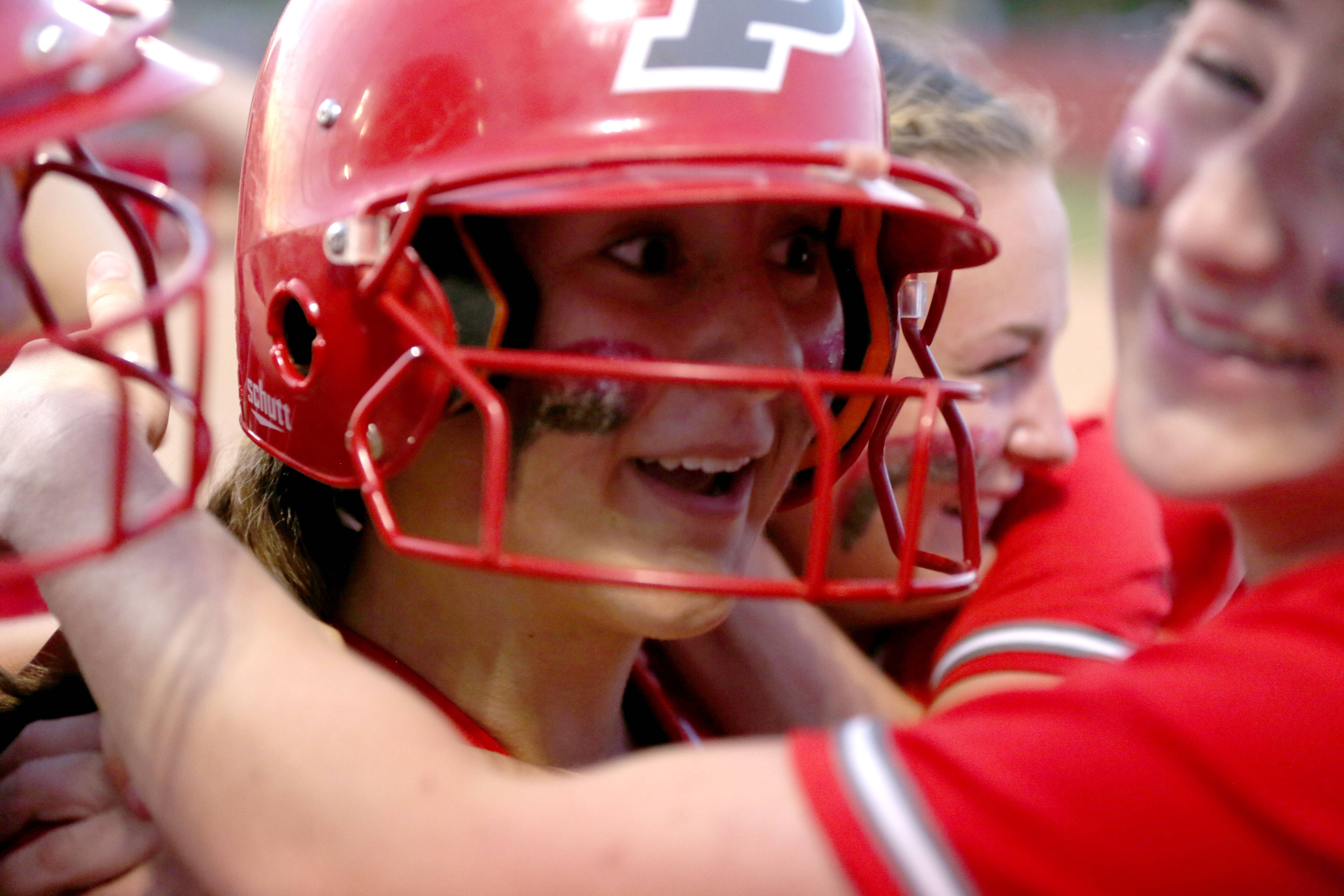 Palatine's Kaitlyn Reed is mobbed by teammates after her 3-run homer during Class 4A supersectional action at Barrington on Monday night.