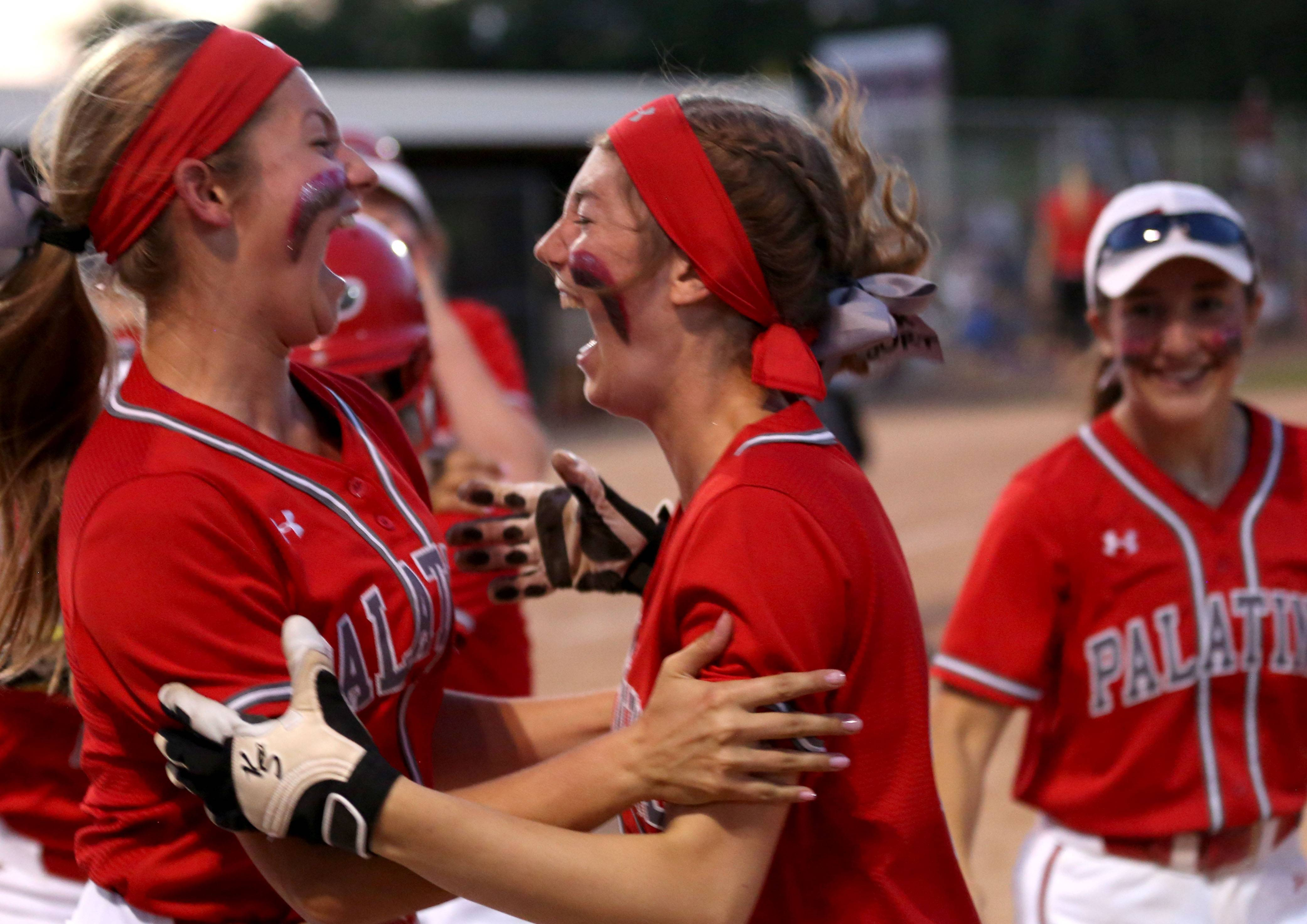 Palatine's Emily Brinckerhoff, left, and Rhiann Dick celebrate a 3-run homer from Emily Parrott in the Class 4A supersectional at Barrington on Monday night.