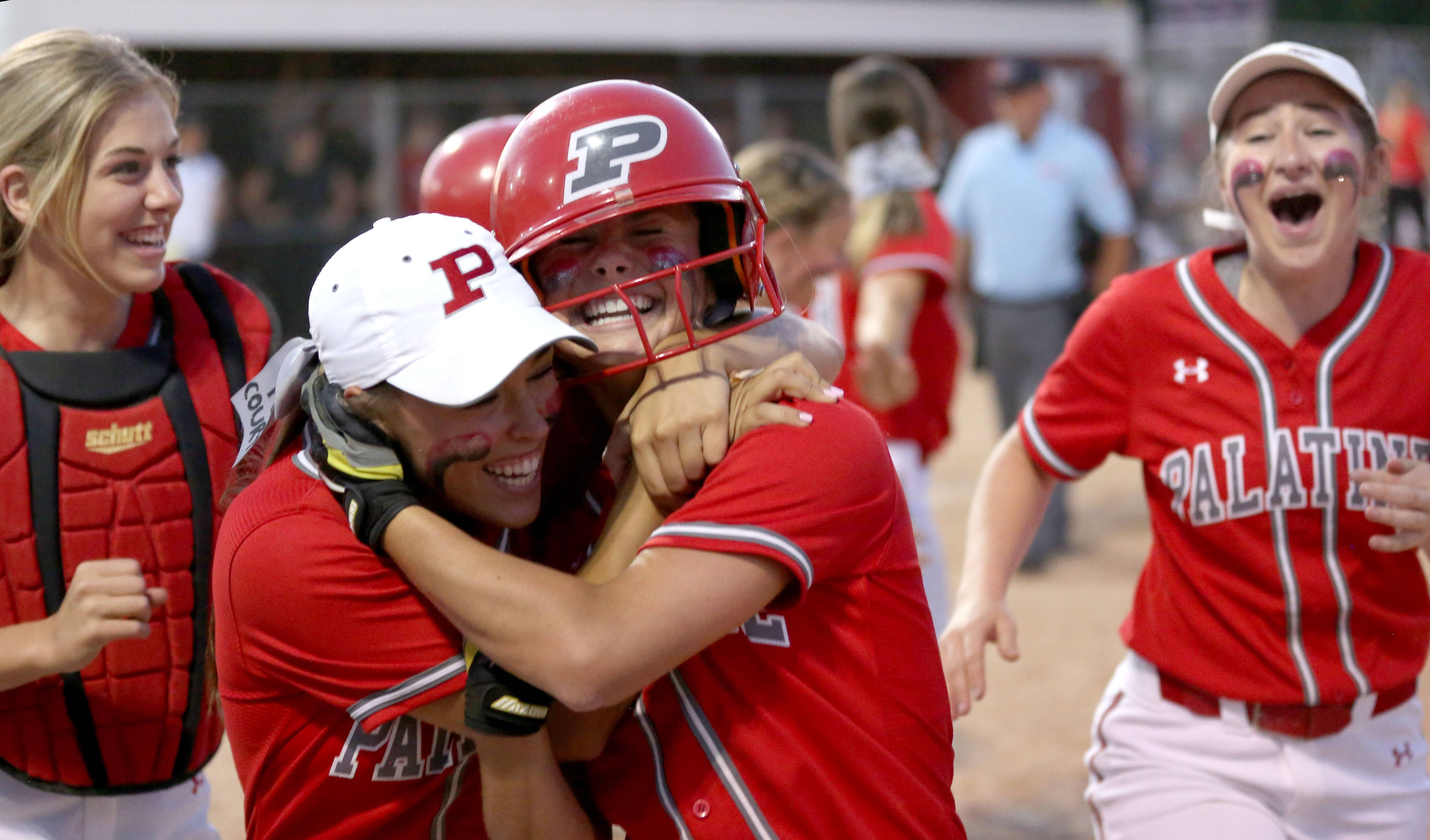 Emily Parrott, center right, is embraced by Brittany Padden after Parrott's 3-run homer in the Class 4A supersectional at Barrington on Monday night.
