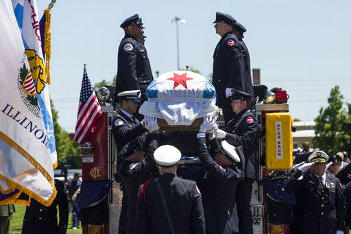 Chicago Fire Department personnel lift Juan Bucio's casket off a fire truck for his funeral at St. Rita of Cascia High School, Monday, June 4, 2018 in Chicago. Bucio, a CFD diver, died on Memorial Day while conducting a search for a boater who fell overboard in the Chicago River. (Ashlee Rezin/Chicago Sun-Times via AP)