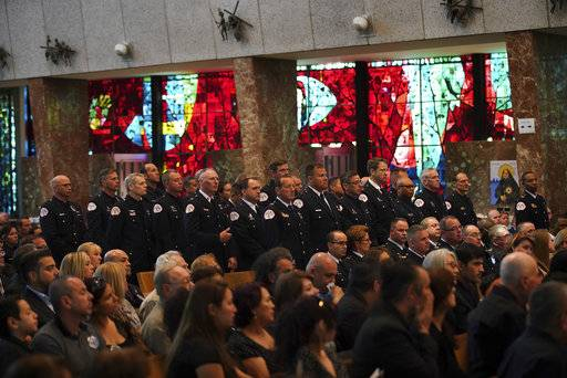 A unit of fallen Chicago Fire Department diver Juan Bucio stand at his funeral at St. Rita of Cascia Shrine Chapel, Monday, June 4, 2018. Bucio died last week while searching for a boater who fell overboard in the Chicago River. (E. Jason Wambsgans/Chicago Tribune via AP, Pool)