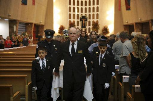 The family of fallen Chicago Fire Department diver Juan Bucio serve as pallbearers at his funeral at St. Rita of Cascia Shrine Chapel, Monday, June 4, 2018. Bucio died last week while searching for a boater who fell overboard in the Chicago River. (E. Jason Wambsgans/Chicago Tribune via AP, Pool)