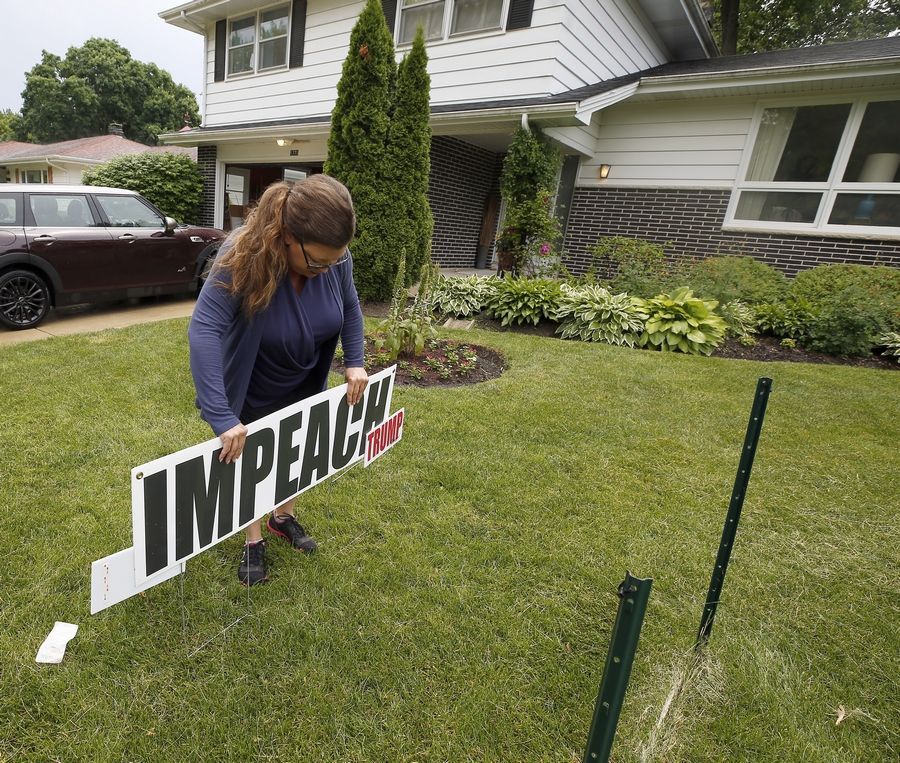 "Kim Gilmore of Gilberts on Wednesday cut down a political sign in her friend Myra Becker's yard in Elgin. The city said the sign was too large under the municipal code. The sign now says ""Impeach Trump"" rather than ""Impeach President Trump Now."""