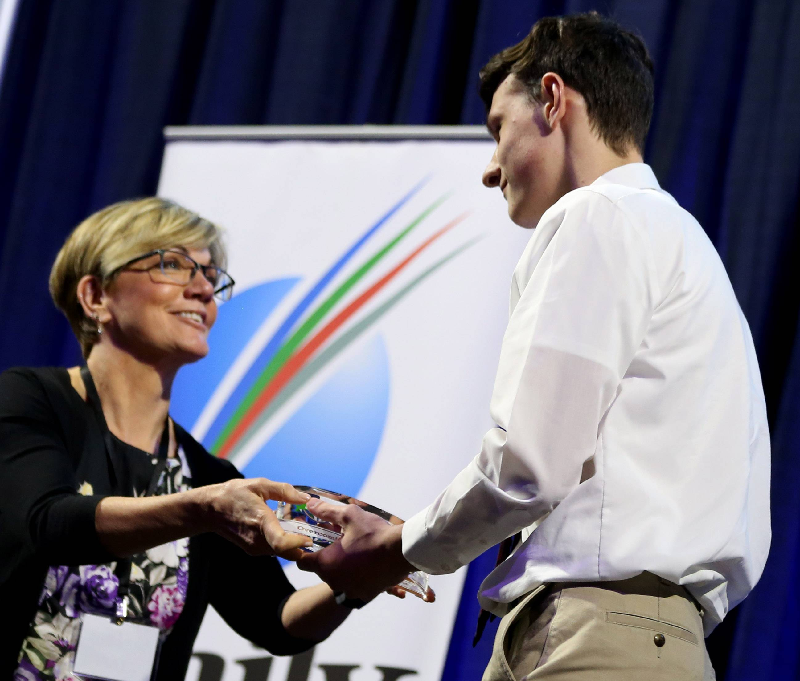 Zach Upp of Wheaton Academy receives the Overcoming Obstacles Award from Eileen Brown of the Daily Herald Media Group on Thursday night as part of the Daily Herald Prep Sports Excellence Awards at the Sears Centre in Hoffman Estates.