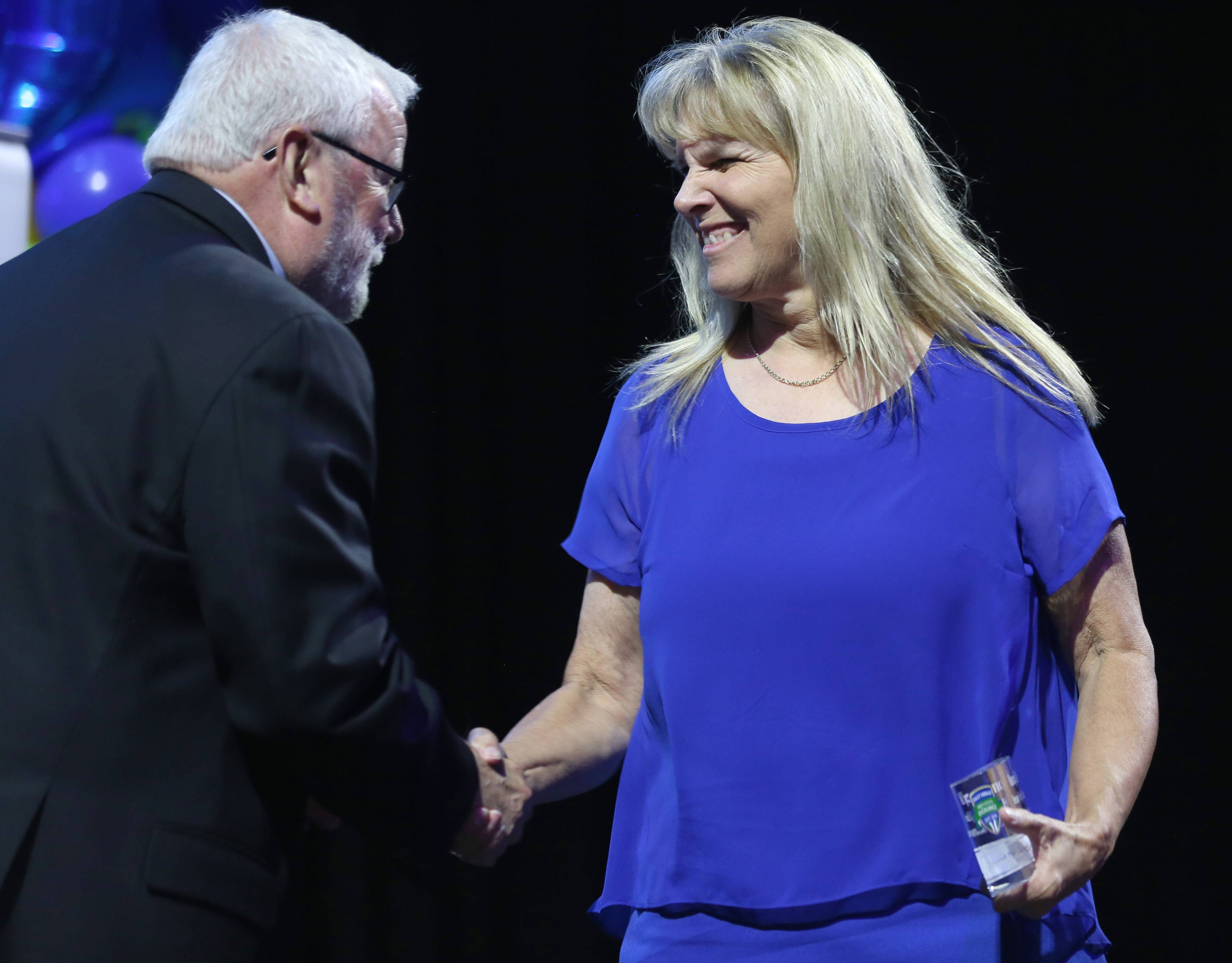 Nancy Lill of Hersey High School shares a moment with Hoffman Estates Mayor Bill McLeod after Lill received the Beyond the Bench Award on Thursday night at the Daily Herald Prep Sports Excellence Awards at the Sears Centre in Hoffman Estate.