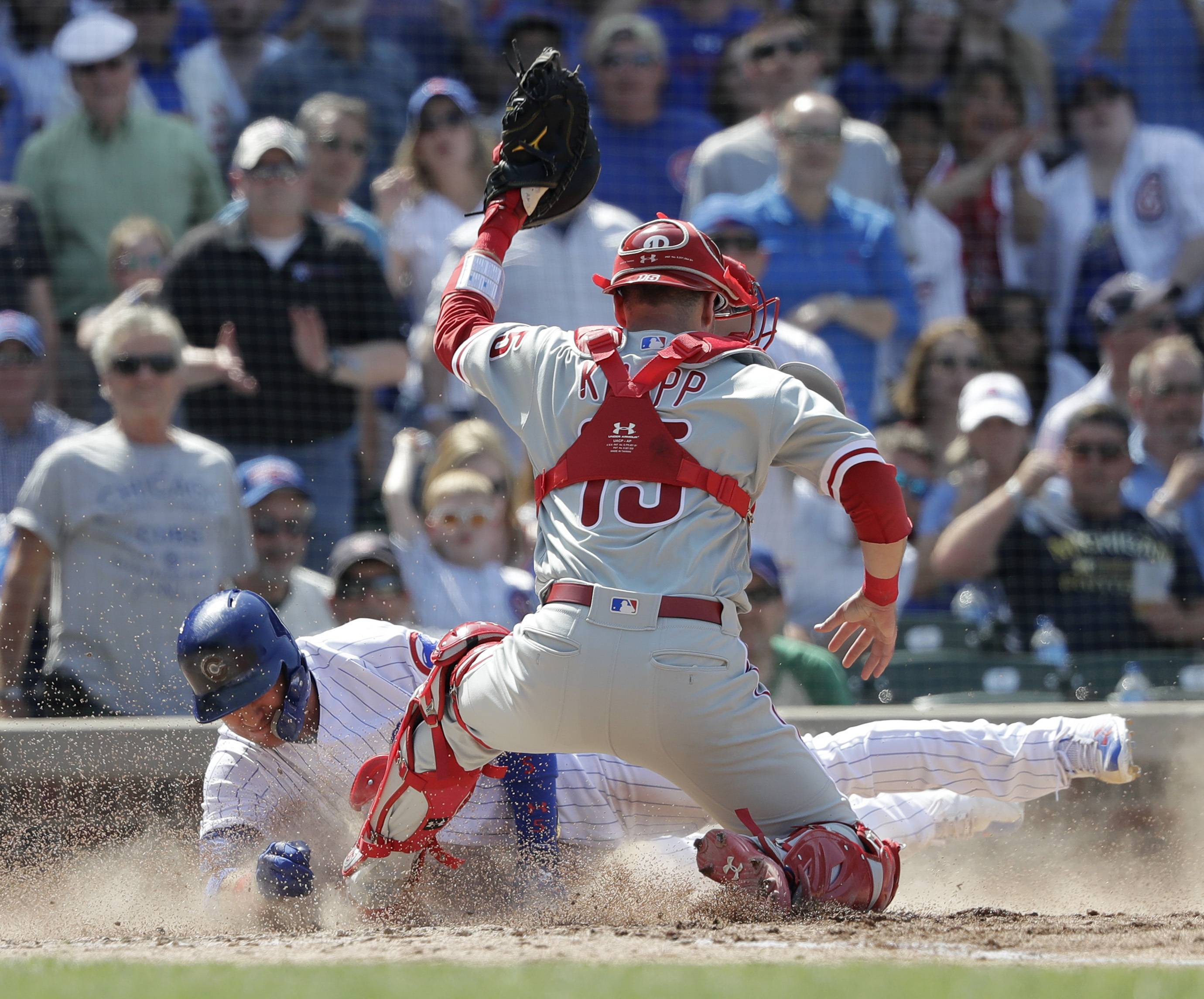 Philadelphia Phillies catcher Andrew Knapp, right, blocks home plate with his left foot and tags out Cubs' Albert Almora Jr. off a sacrifice fly by Anthony Rizzo during the fifth inning on Thursday at Wrigley Field. The play was overturned by video review with Knapp called for catcher interference.