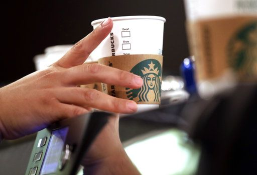 FILE- In this May 29, 2018, file photo, a barista reaches for an empty cup at a Starbucks, commonly referred to as the original Starbucks, in the Pike Place Market in Seattle. Starbucks says it's raising the price of a regular drip coffee by 10 cents to 20 cents this week in most U.S. stores. It says a small brewed coffee is now $1.95 to $2.15 in a majority of locations. The company said Thursday, June 7, 2018, that prices remain unchanged on drinks such as lattes and iced coffees in most stores.