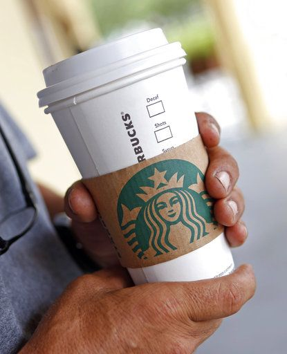FILE- In this Aug. 10, 2017, file photo, a person holds a beverage from a Starbucks in Miami Springs, Fla. Starbucks says it's raising the price of a regular drip coffee by 10 cents to 20 cents this week in most U.S. stores. It says a small brewed coffee is now $1.95 to $2.15 in a majority of locations. The company said Thursday, June 7, 2018, that prices remain unchanged on drinks such as lattes and iced coffees in most stores.