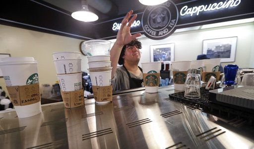 FILE- In this May 29, 2018, file photo, barista Christian Moreno calls for an order as he stands behind a row of coffee cups ready to be filled in Seattle. Starbucks says it's raising the price of a regular drip coffee by 10 cents to 20 cents this week in most U.S. stores. It says a small brewed coffee is now $1.95 to $2.15 in a majority of locations. The company said Thursday, June 7, 2018, that prices remain unchanged on drinks such as lattes and iced coffees in most stores.