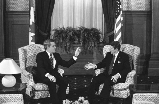 FILE- In this March 17, 1985, file photo, Canadian Prime Minister Brian Mulroney and U.S. President Ronald Reagan hold their first round of talks in Quebec City, Quebec. When Reagan visited Canada, he was so friendly with then Prime Minister Brian Mulroney they sang a song together. When President Donald Trump visits this week there's speculation he could walk out of meetings with allies furious over his belligerent trade policies.