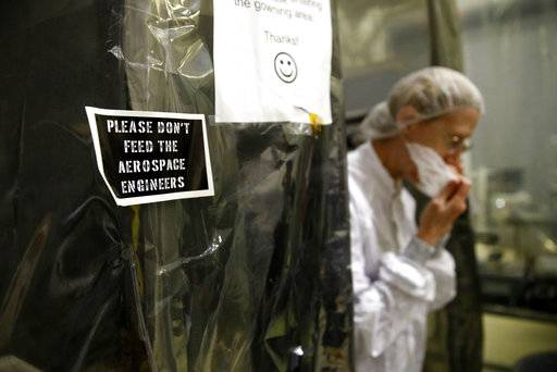 In this April 30, 2018 photo, a sign greets visitors at the entrance to a cleanroom as cryogenics manager Susan Breon adjusts her face mask at NASA's Goddard Space Flight Center in Greenbelt, Md. A scientist by day, Breon plays the keyboard for a musical production put on by the center's music and drama club.