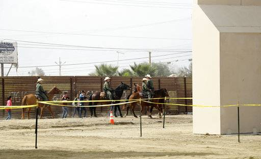 FILE - In this Oct. 19, 2017, file photo, a group of people are detained by Border Patrol agents on horseback after crossing the border illegally from Tijuana, Mexico, near where prototypes for a border wall, right, were being constructed in San Diego. More than 1,600 people arrested at the U.S.-Mexico border, including parents who have been separated from their children, are being transferred to federal prisons, U.S. immigration authorities confirmed Thursday, June 7, 2018. They said they're running out of room at their own facilities amid President Donald Trump's crackdown on illegal immigration. The move drew condemnation from activists who said the detainees may have legitimate claims to asylum and don't deserve to be held in federal prisons.