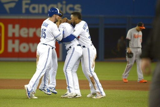 Toronto Blue Jays' Aledmys Diaz, center, is met by teammates Randal Grichuk, left, and Teoscar Hernandez after hitting a walk-off single against the Baltimore Orioles during 10th inning of a baseball game Thursday, June 7, 2018, in Toronto. Toronto won 5-4. (Jon Blacker/The Canadian Press via AP)