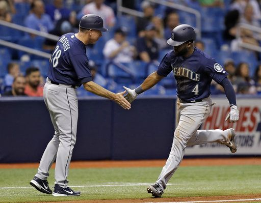 Seattle Mariners' Denard Span (4) shakes hands with third base coach Scott Brosius after Span hit a home run off Tampa Bay Rays relief pitcher Austin Pruitt during the third inning of a baseball game Thursday, June 7, 2018, in St. Petersburg, Fla.