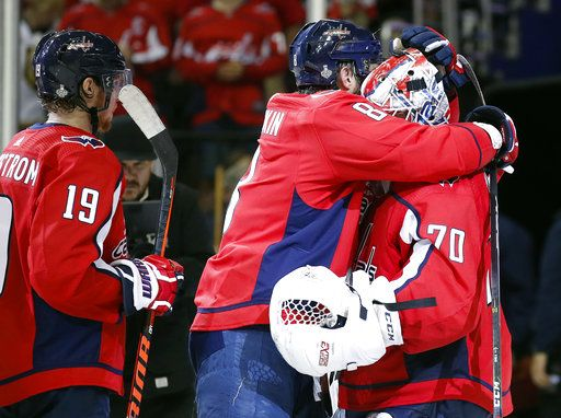 Washington Capitals forward Alex Ovechkin, center, of Russia, celebrates with goaltender Braden Holtby, right, after the team's 3-1 victory over the Vegas Golden Knights in Game 3 of the NHL hockey Stanley Cup Final, Saturday, June 2, 2018, in Washington. At left is Capitals forward Nicklas Backstrom, of Sweden.