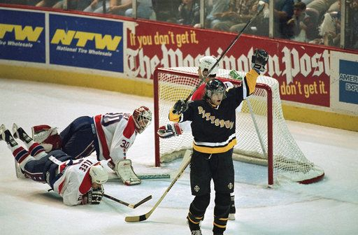 FILE - In this May 12, 1995, file photo, Pittsburgh Penguins; Jaromir Jagr, right, celebrates his first period goal  in front of Washington Capitals goaltender Jim Carey (30) and Kevin Klee (2), during an NHL hockey game in Landover, Md. It's as though all the bad breaks from the previous 42 seasons of Washington Capitals hockey are being erased - or at least somewhat forgotten - in a run that could deliver the franchise's first title. The Capitals lead Vegas three games to one in the best-of-seven Stanley Cup Finals. Game 5 is Thursday, June 7, 2018.