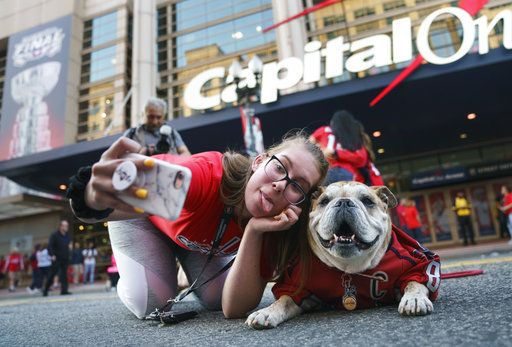 A Washington Capitals fan poses for a photo with Ovie the Bulldog outside Capitol One Arena before Game 4 of the NHL hockey Stanley Cup Final between the Capitals and the Vegas Golden Knights, Monday, June 4, 2018, in Washington.